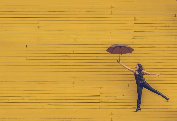 a girl jumping with a red umbrella against a yellow wall