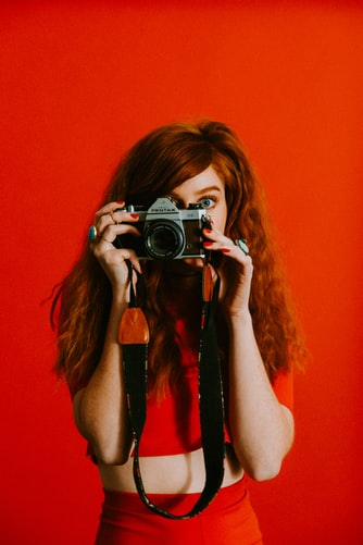 a girl wearing red with a camera