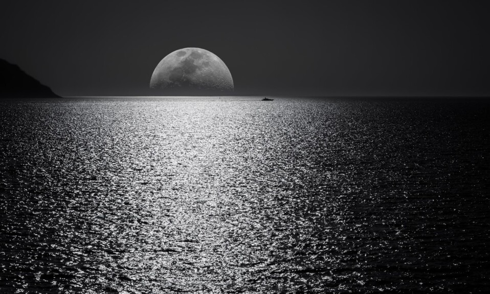 Monochrome image of a boat on the sea next to the shining moon