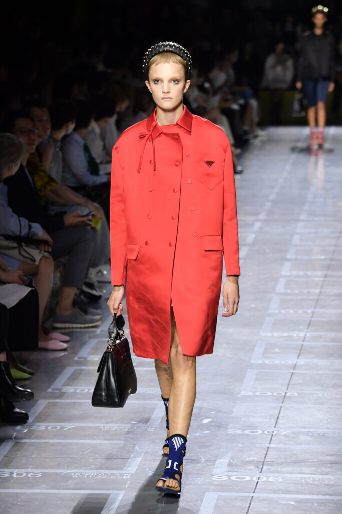 a girl with a long coat in living coral