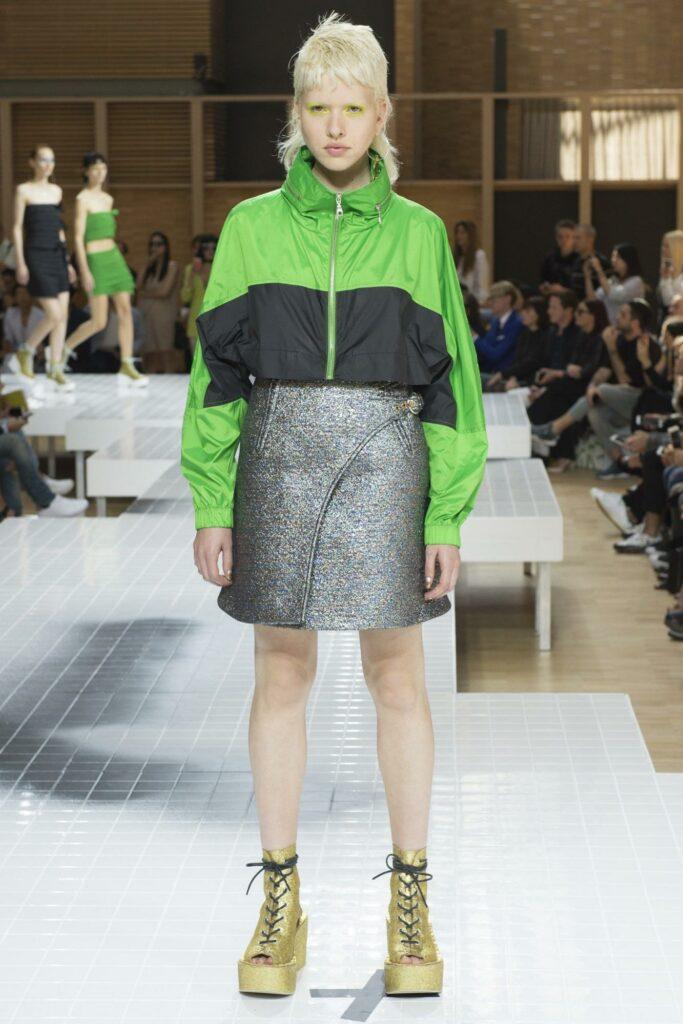 a girl that wear a coat in greenery
