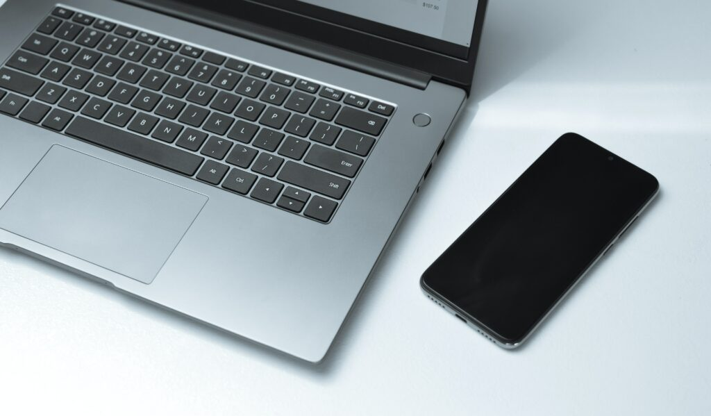 image of a gray laptop and cell phone to show the usage of  Gray color in Marketing and branding