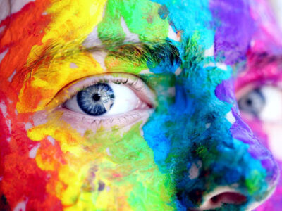 a boy with a face painted in the colors of the rainbow and blue eyes