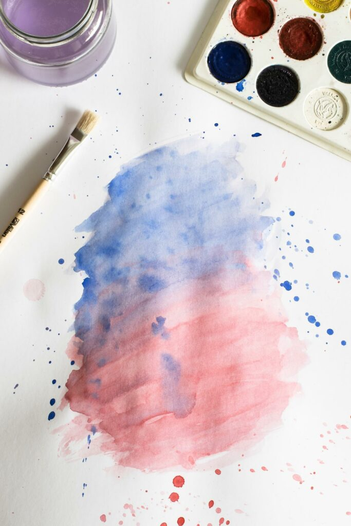 Watercolor and painting brush with pink and pastel blue design on paper