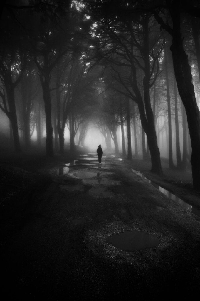 a girl in the foggy forest with fear emotions in monochrome color photography