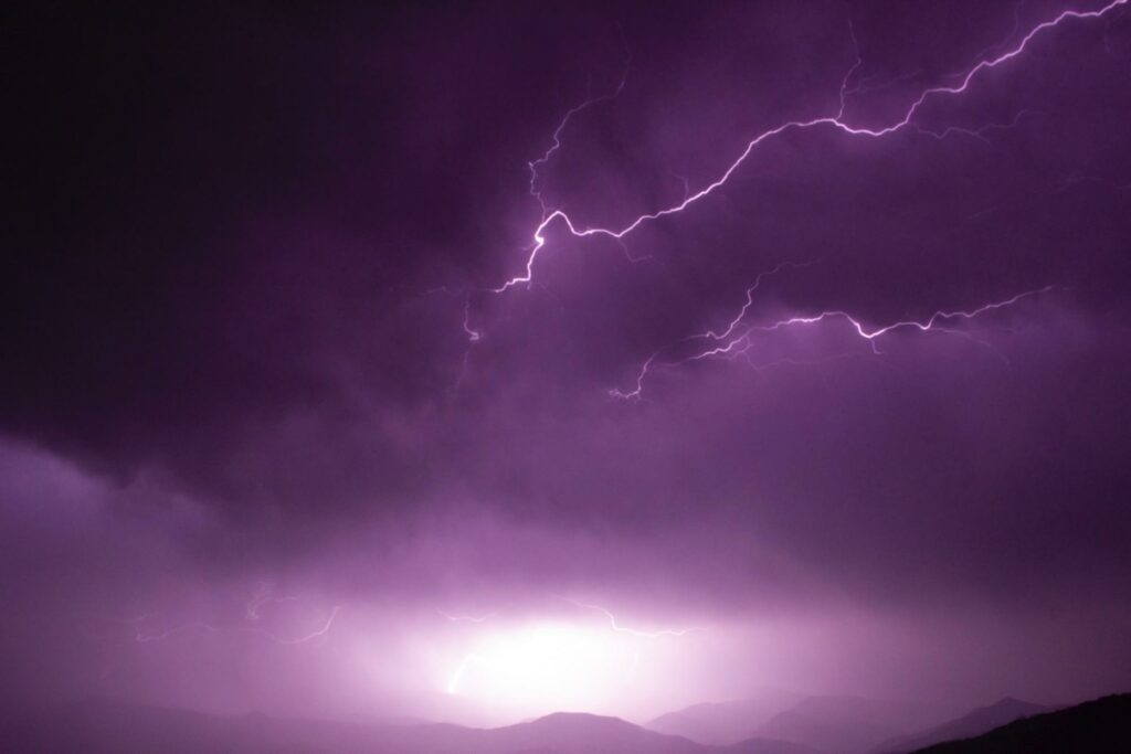 monochrome color photography of purple thunder in the sky