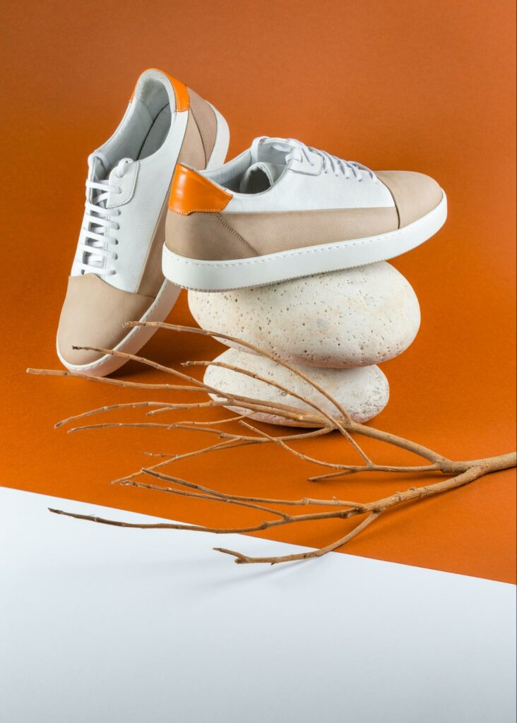 commercial photography of a pair of shoes next to two stones and a stick on an orange background