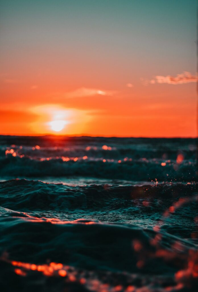 color photography of sunset and sea wave