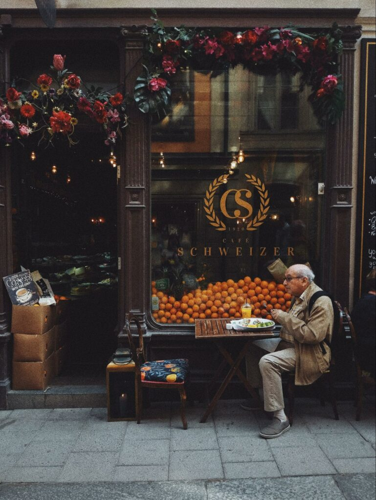 color photography of an old man sitting in a cafe