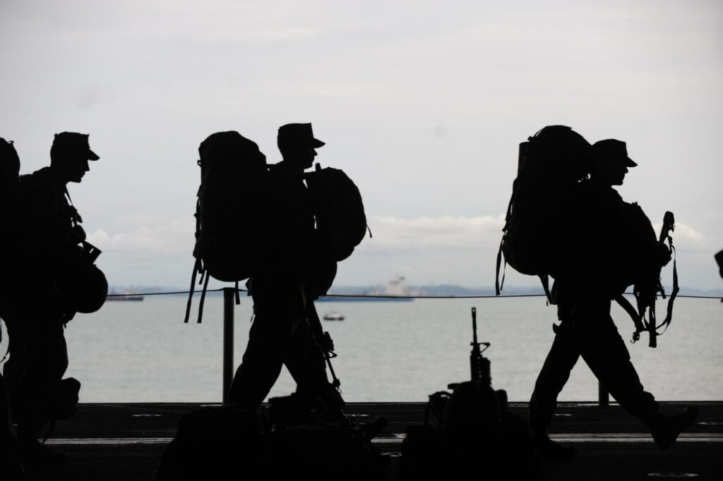 three soldiers and their backpacks