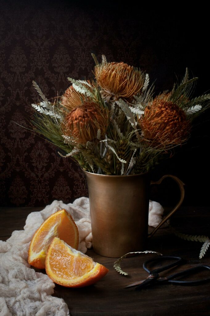 a vase full of flowers with oranges and scissors on the table