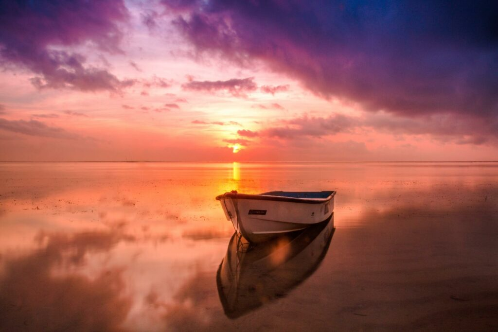 boat by the beach at sunset