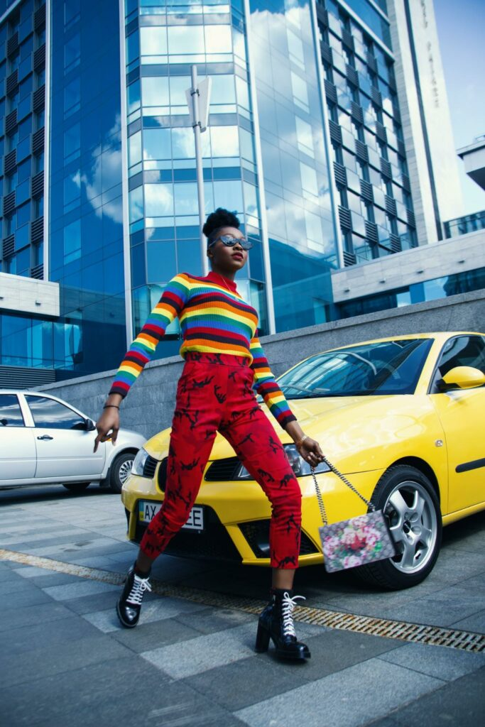 fashion photography of a girl on the street in a rainbow dress and red pants