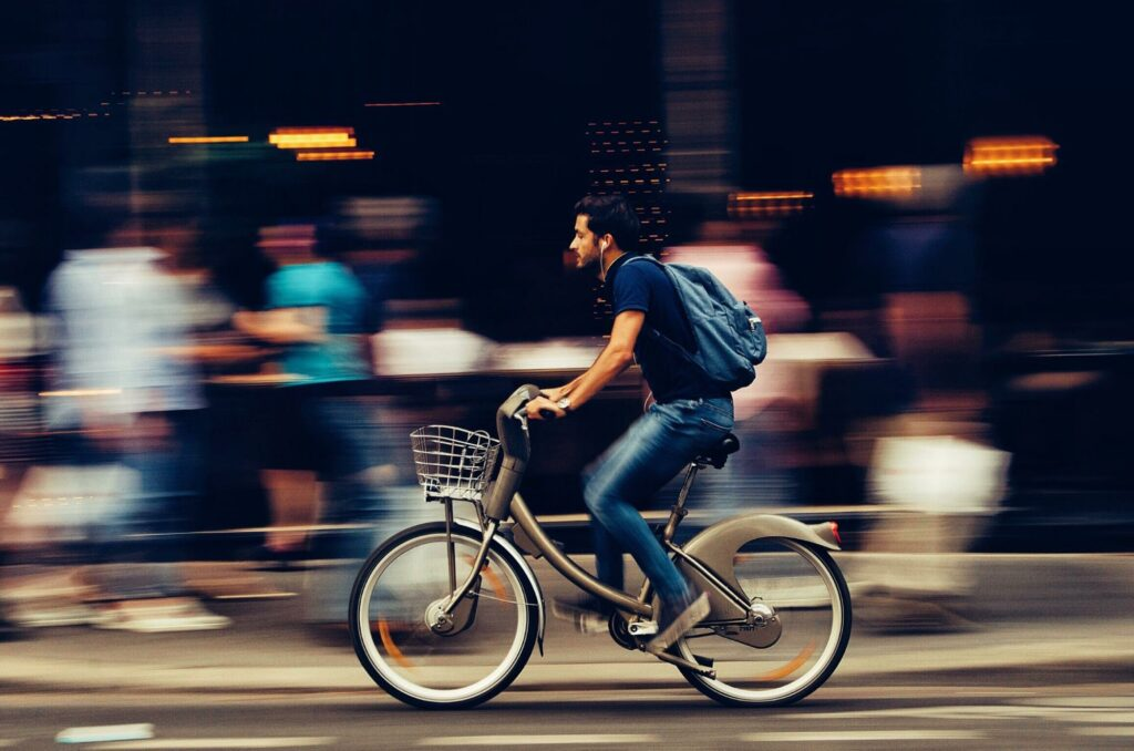 time lapse photography of a boy sitting on his bicycle on the street