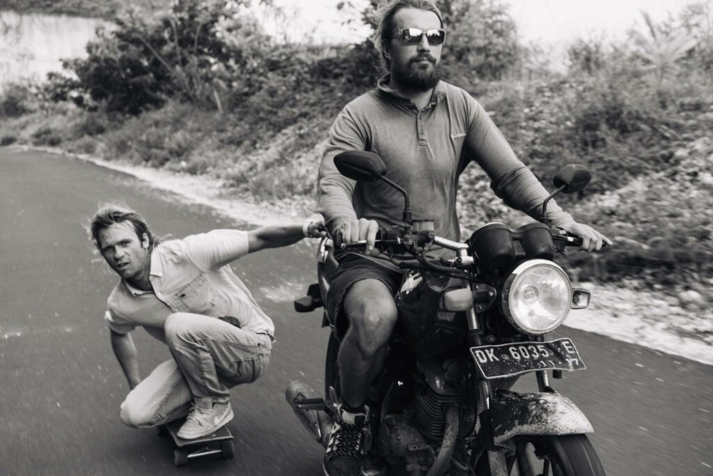 two men riding motorcycles on the road