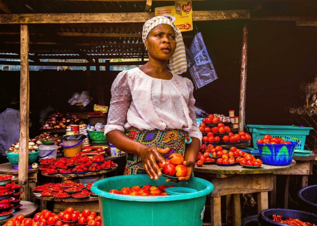 african woman washing tomatoes in the market