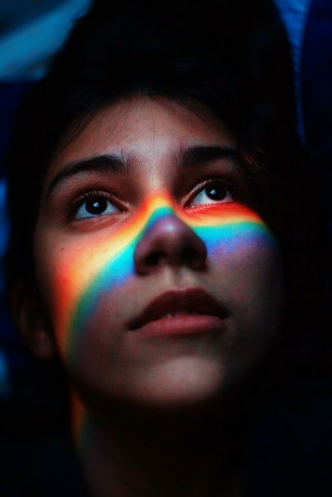 portrait of a girl with a rainbow on her face