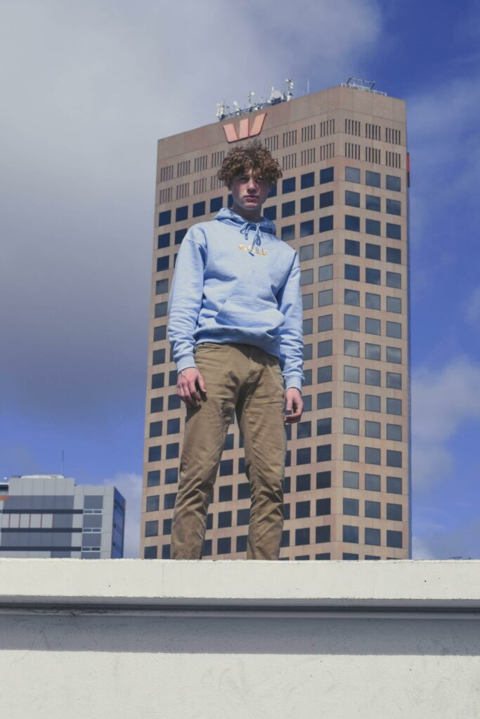 a boy standing in front of a tall building