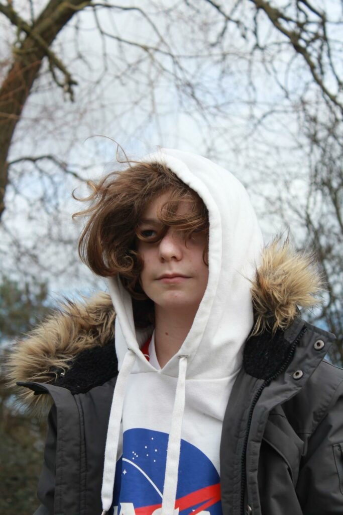 a boy put on white hoodie and jacket