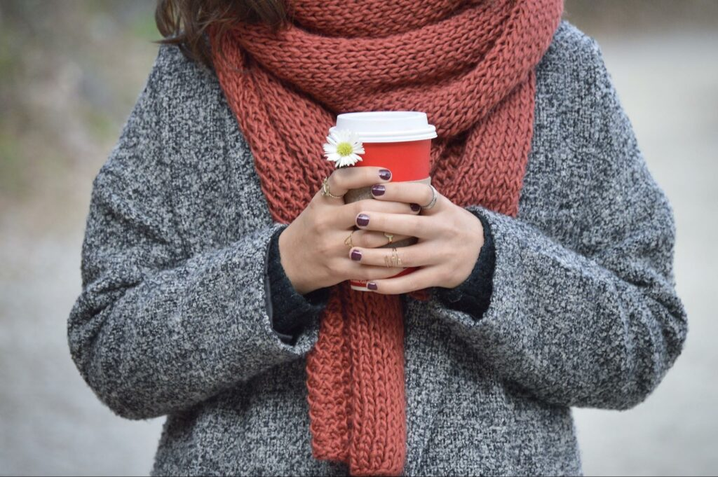 a girl that put on a scarf for winter