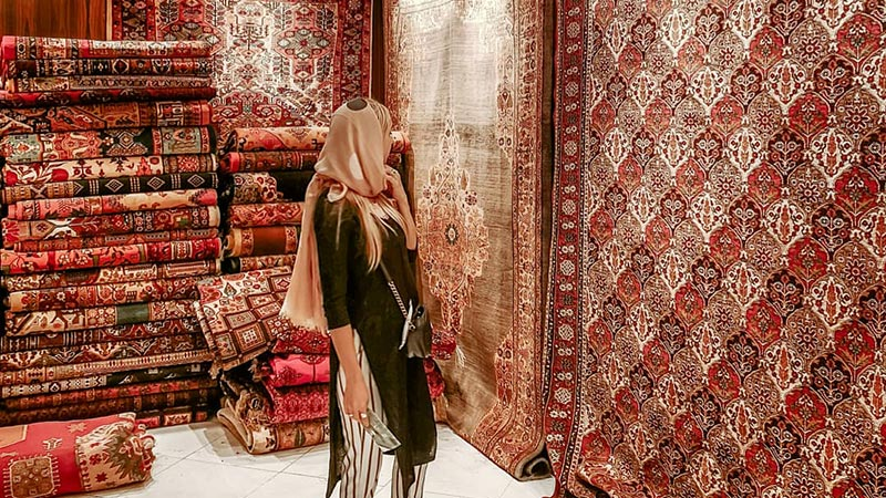 There is a Persian woman standing in front of a carpet store filled with brown Persian rugs with auntie patterns
