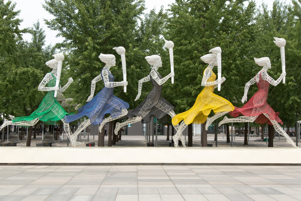 statue of five women with running torches wearing clothes in the color of the rings of the Olympic symbol