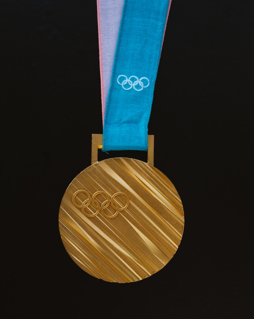 Olympic gold medal with five interlocking rings engraved on it.
