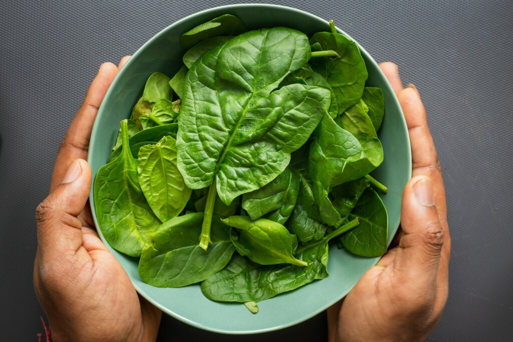 spinach in a bowl in a man's hand