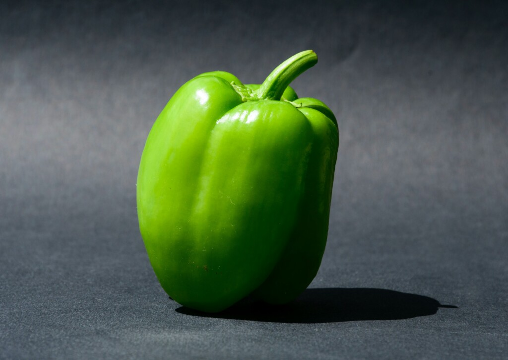 one green bell pepper on black background
