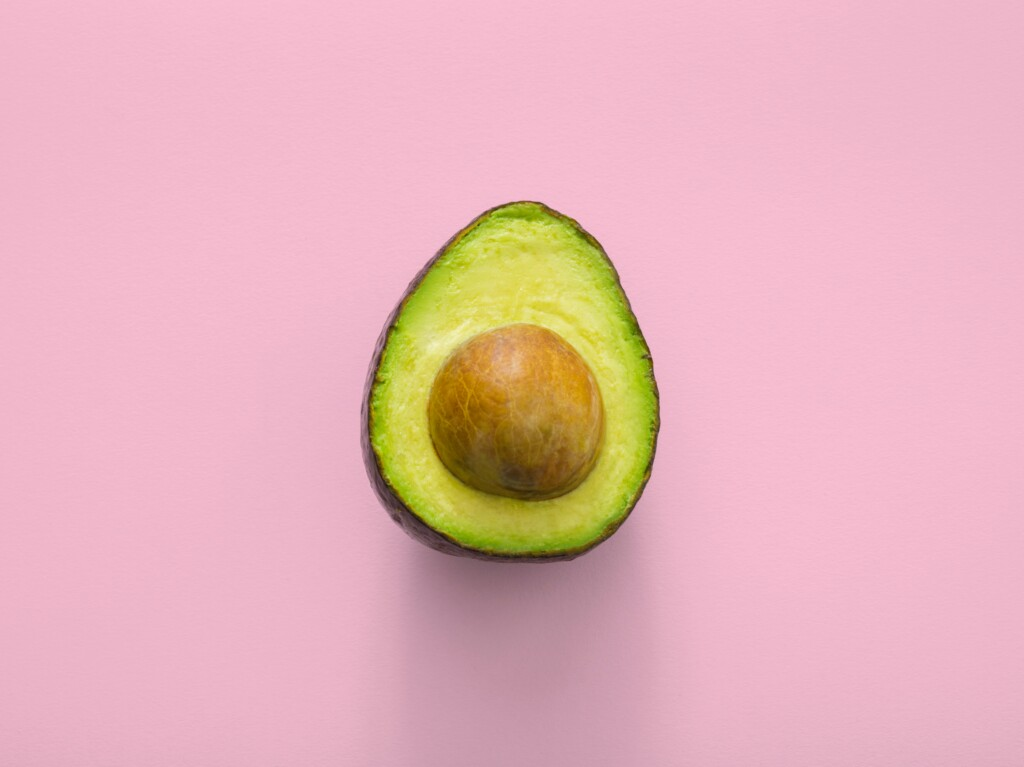 one avocado in pink background