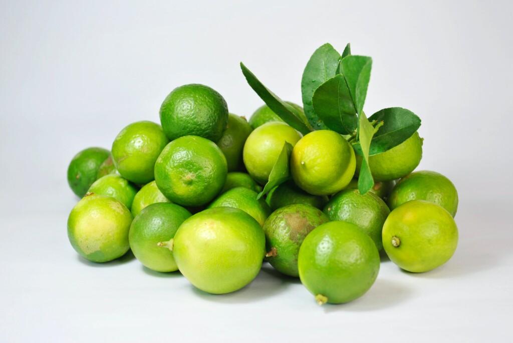 a few green lemons on a white background