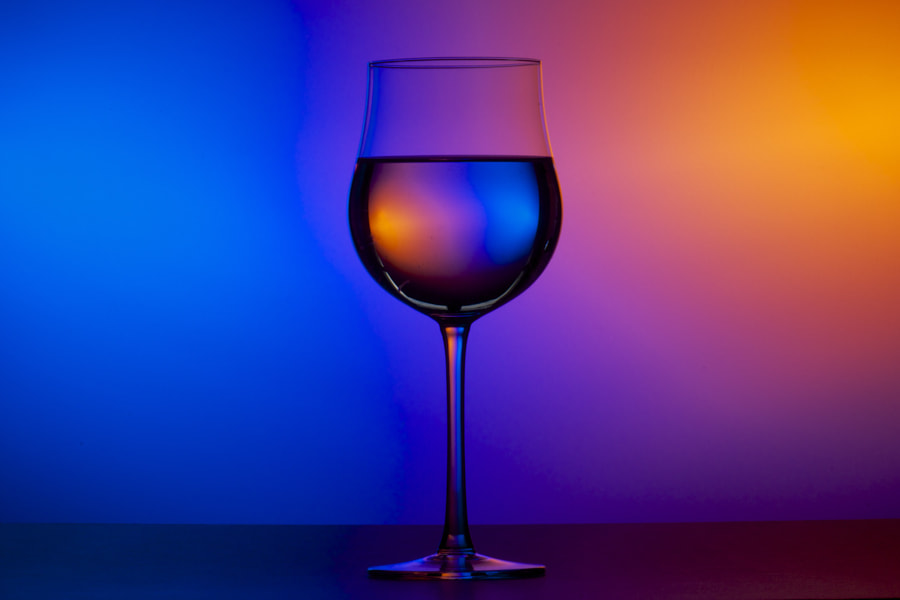blurry blue and orange colors in the background, a glass in front of it