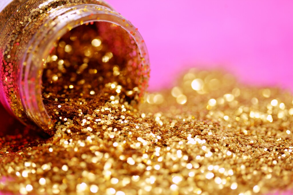 golden wreaths poured from a bottle on a pink background