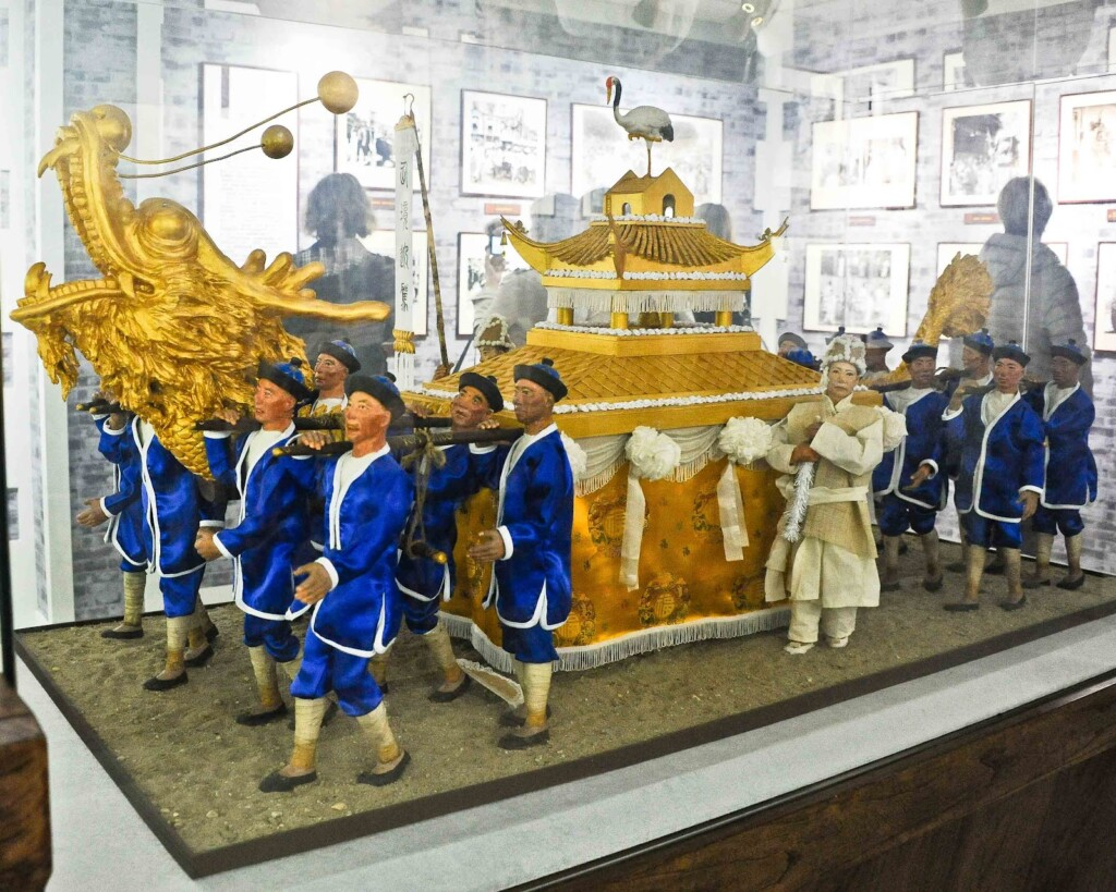 a photo of a replica of a golden coffin at a funeral in chinese culture carried by  people in white and blue