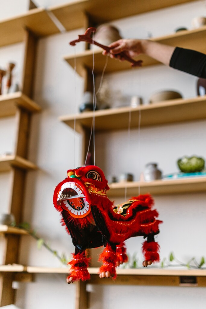 chinese red dragon doll hanging from a woman's hand