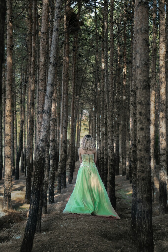 a girl in a green wedding dress in the middle of the forest