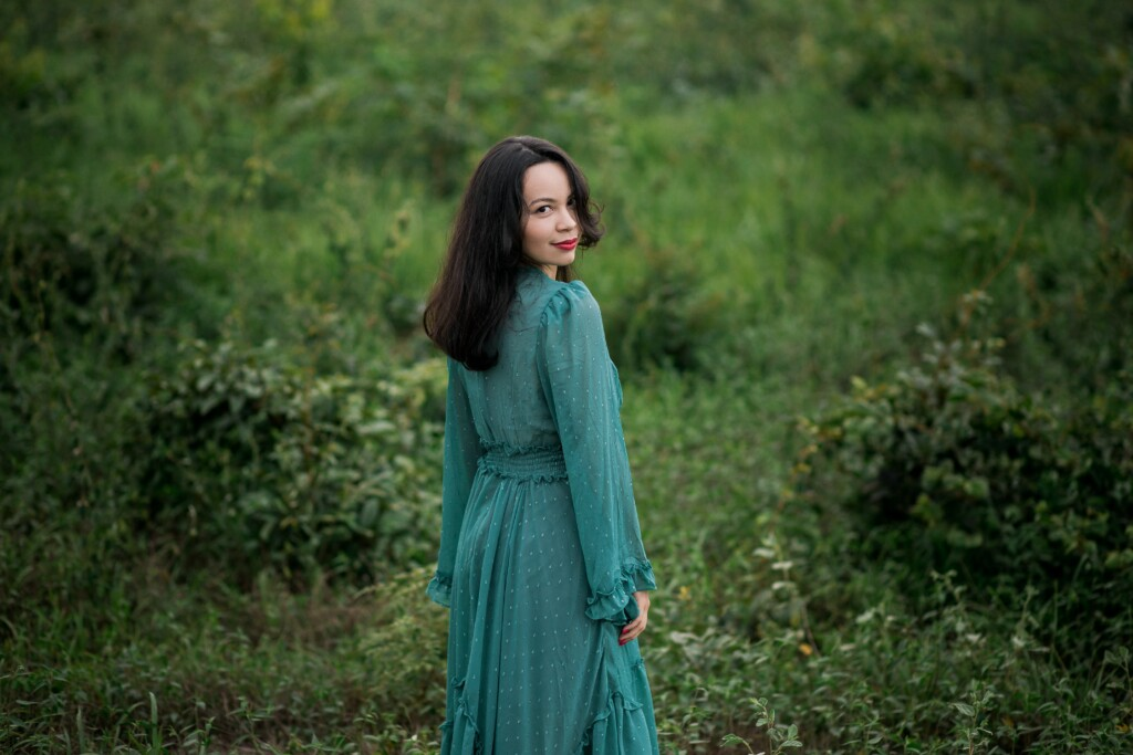 a girl in a green dress in the green nature
