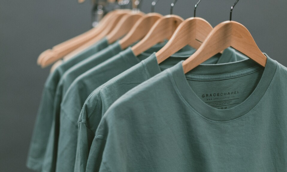 green T-shirts hanging on clothes hangers