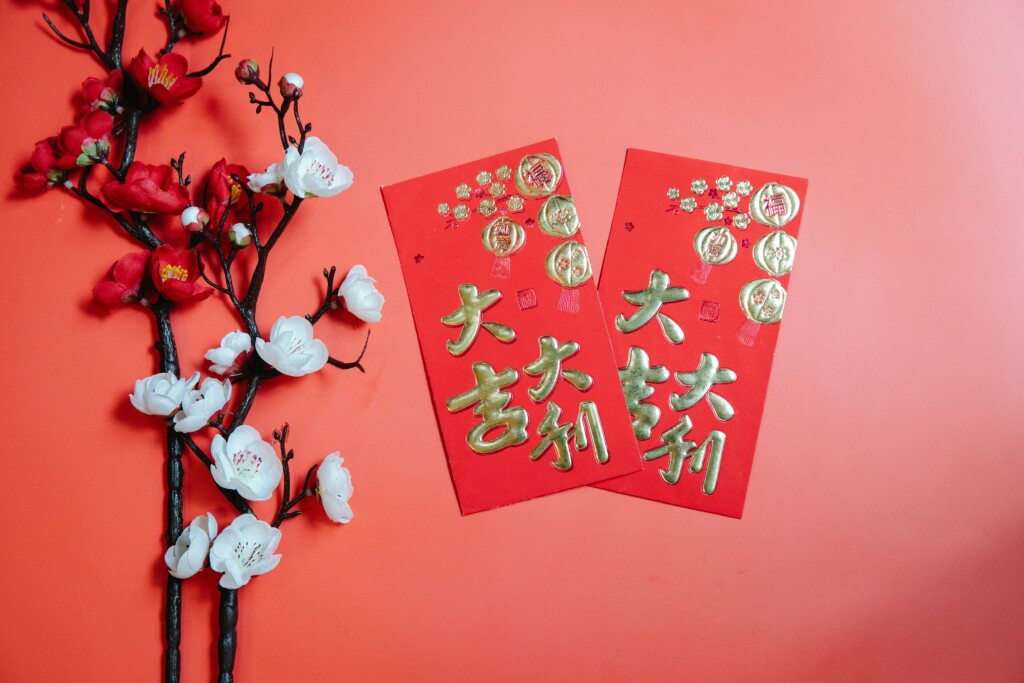 two red and gold postcards written in Chinese letters on a reddish background with white and red artificial flowers
