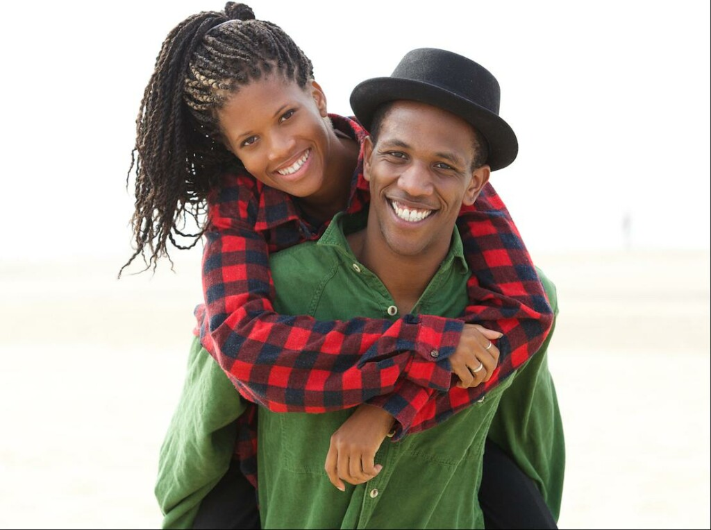 picture of a woman in a red and black plaid shirt holding a man in a green shirt and black hat