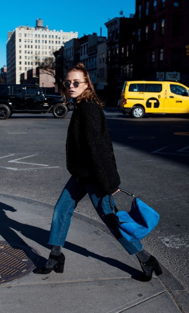girl wearing black coat and blue jeans with blue bag