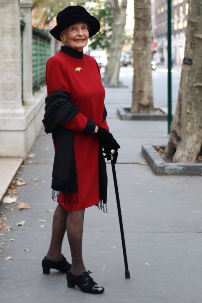 old woman wearing red and black outfit