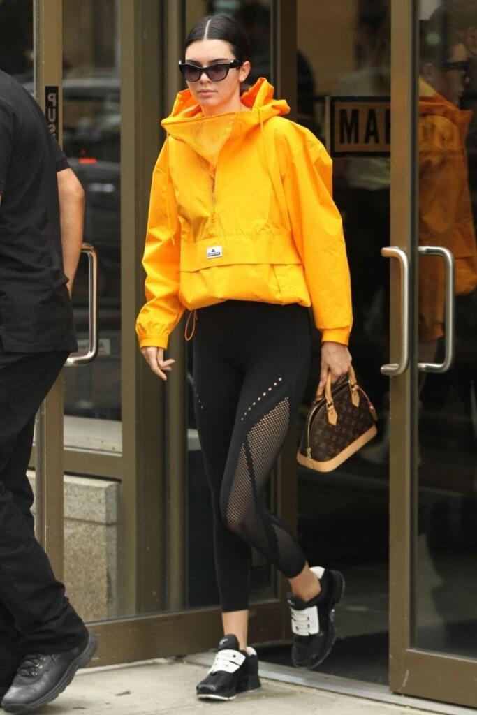 girl wearing yellow hoodie and black pants