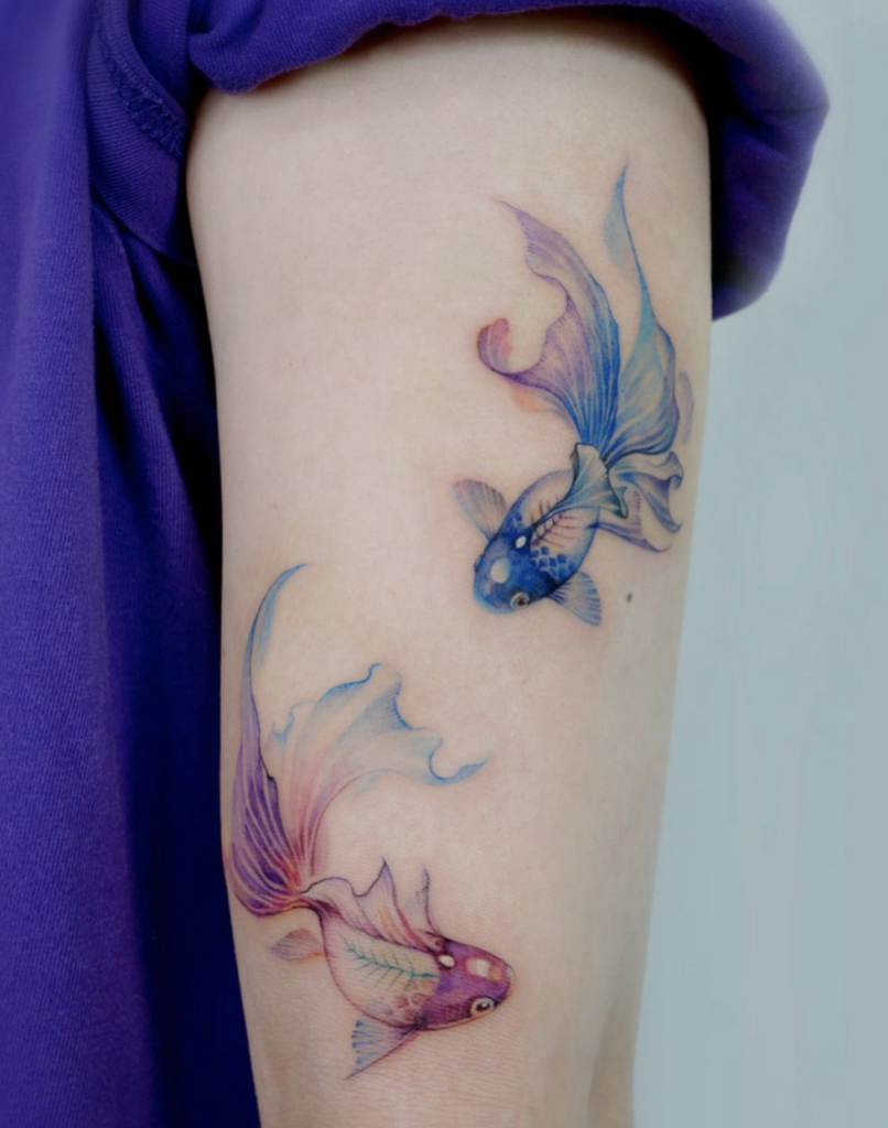 tattoo of two fishes on the forearm with blue and purple tattoo colors