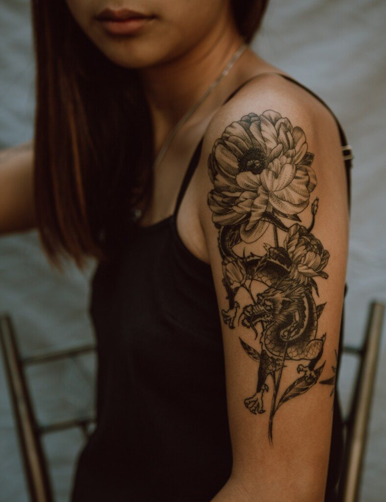 tattoo of flower and dragon on the girl's forearm on dark skin