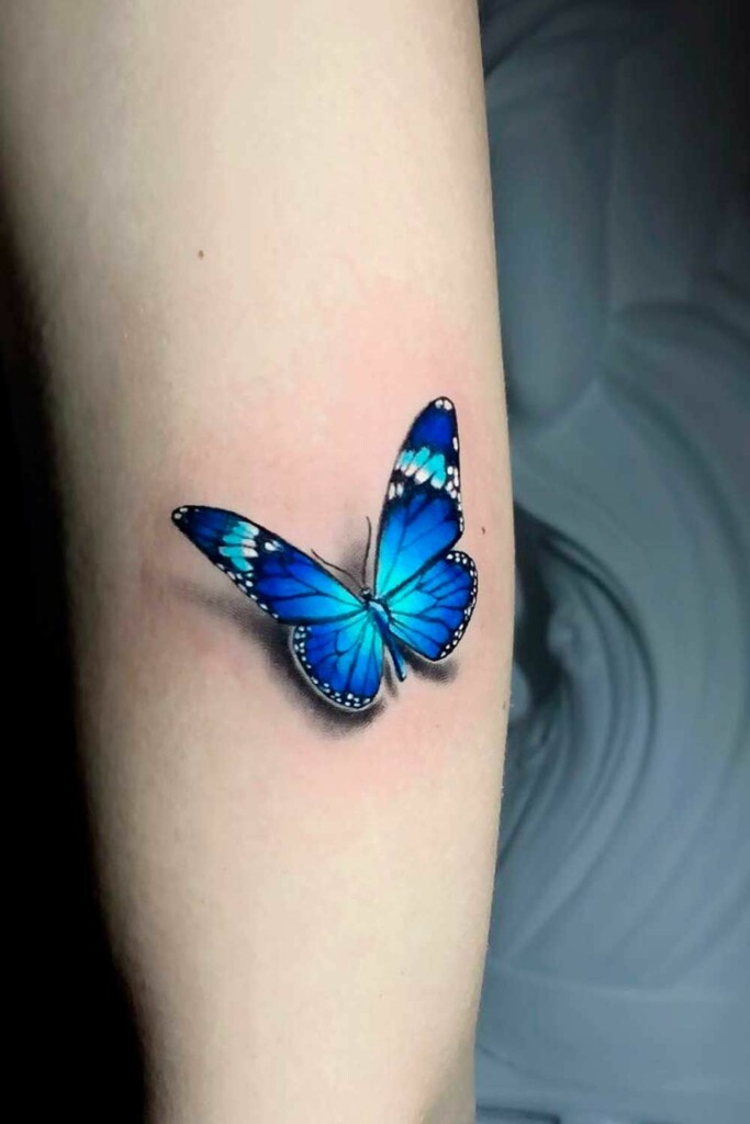 blue butterfly tattoo on girl's arm