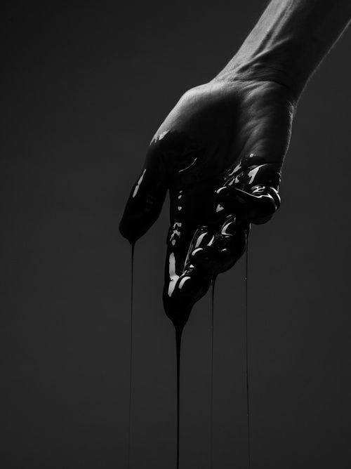 black and white photo of human hand covered by black color