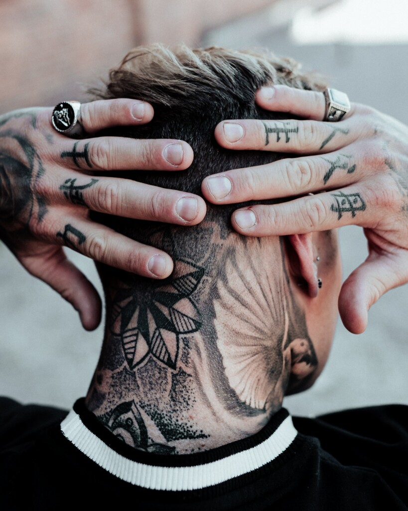 man with black tattoos on the neck and Chinese script on the fingers
