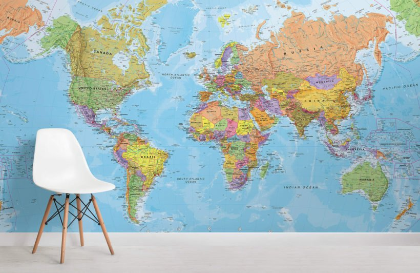 Colorful world map on a wall with a white chair in front of it