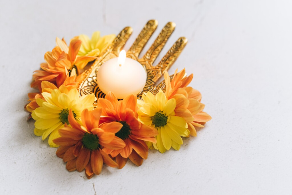an image of a golden hand-shaped candle holder with a white candle on it. also orange and yellow flowers around it.